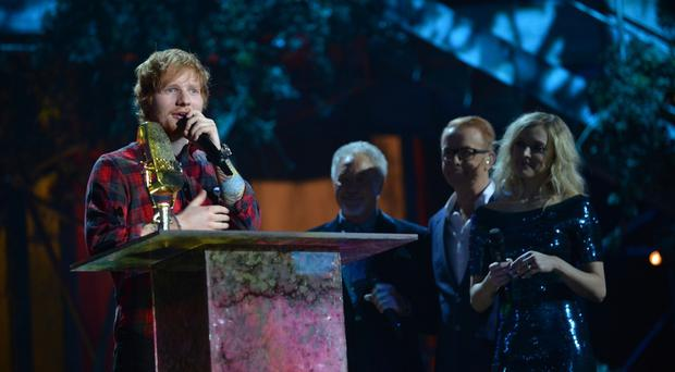 Ed Sheeran collects the British artist of the year award at the BBC Music Awards at Earl's Court, London