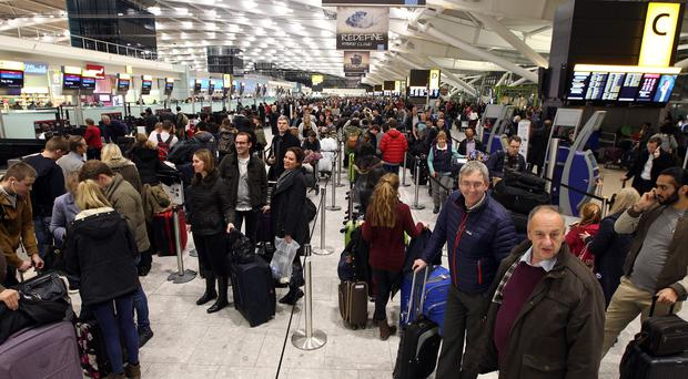 People wait at Terminal 5 of Heathrow Airport as dozens of flights were cancelled nationwide after a computer failure at air traffic control company Nats