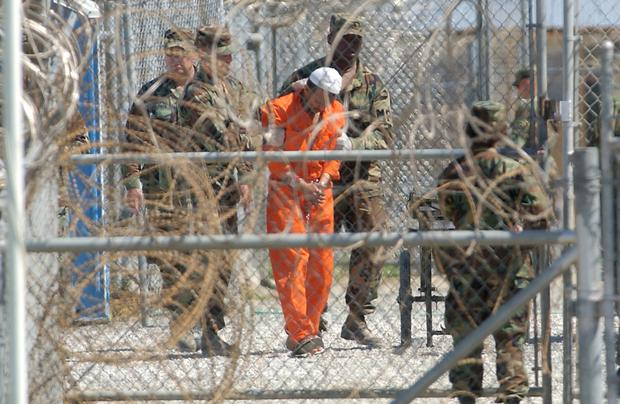 A detainee from Afghanistan is led by military police with his hands chained at Camp X-Ray at the US Naval Base in Guantanamo Bay, Cuba