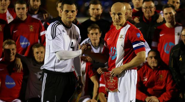 Captains Sgt Keith Emmerson (right) and MSgt Alexander Hess shake hands before the match