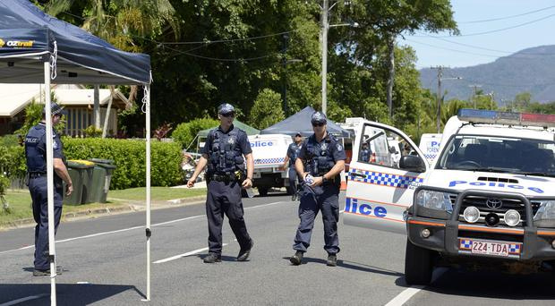 Police patrol near a house where eight children have been found dead in a Cairns suburb. (AP)