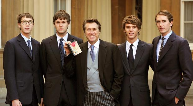 Merlin Ferry, left, with his siblings and father Bryan Ferry when the singer received his CBE at Buckingham Palace