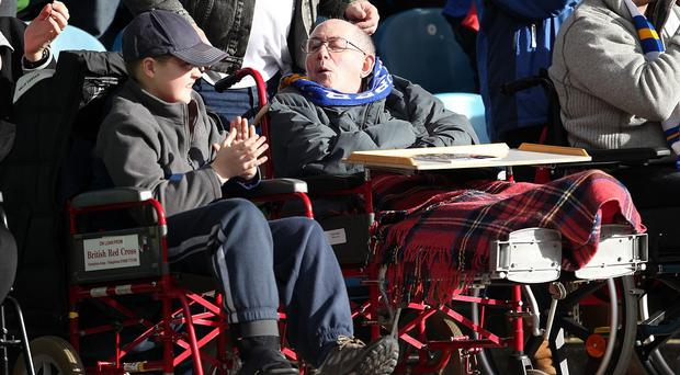 Fans in wheelchairs watch the action