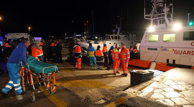 Paramedics wait for rescued passengers from the ferry (AP)