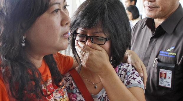 A relative of Air Asia flight QZ8501 passengers weep as she waits for the latest news on the missing plane at Juanda International Airport in Surabaya, East Java, Indonesia (AP)