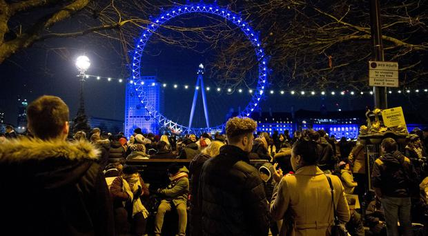 Crowds begin to gather on the Embankment in central London, for the New Year celebration fireworks display at the London Eye, in central London.