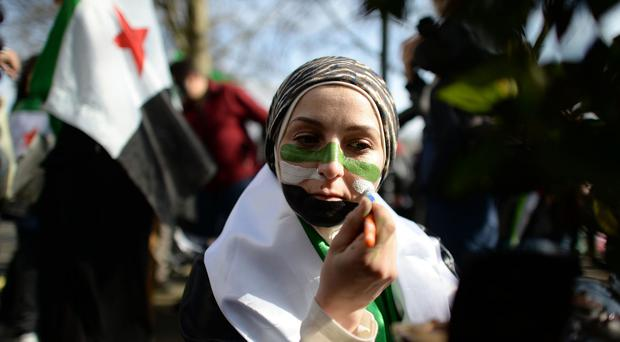 A protester campaigning for more international involvement in the Syrian conflict, as it was revealed that more than 76,000 died in the conflict last year