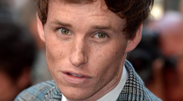 Eddie Redmayne has topped a list of best-dressed men compiled for GQ