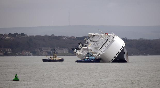 Two tug boats surround the car carrier Hoegh Osaka after she became stranded on Bramble Bank