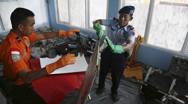 Members of Indonesian Search and Rescue Agency hold a piece which Indonesian Air Force confirmed as from AirAsia Flight 8501 at Disaster Victim Identification room in Pangkalan Bun (AP)