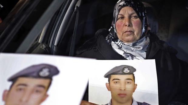 The mother of Jordanian pilot Lt. Mu'ath al-Kaseasbeh holds a picture of her son (AP)