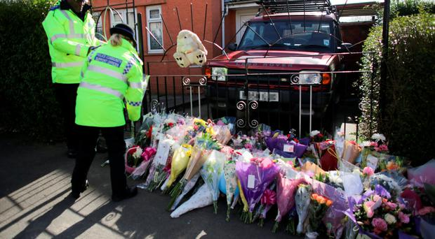 Police officers rearrange flowers outside the home of Becky Watts