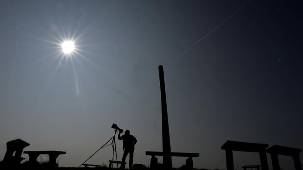 A photographer takes test shots with solar filters in Newcastle, ready for today's eclipse