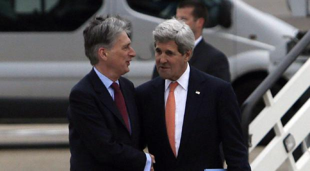US Secretary of State John Kerry (right) is greeted by Foreign Secretary Philip Hammond as he arrives at Heathrow Airport