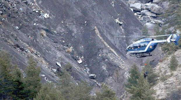A rescue helicopter flies over the debris of the Germanwings jet on the mountainside near Seyne les Alpes (AP)