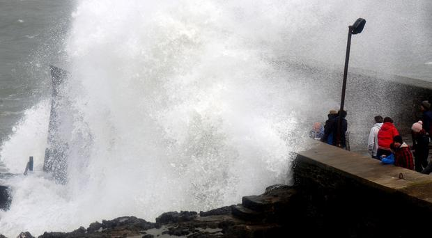 Onlookers watch as waves crash into the harbour at Ilfracombe, North Devon, as the forthcoming Easter break threatens to become a wet and windy washout in Britain.