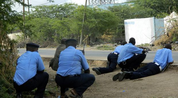 Kenyan police officers take cover outside the Garissa University College during an attack by gunmen (AP)