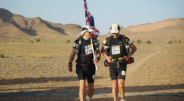 Sir Ranulph Fiennes (right) and his trainer Rory Coleman crossing the finish line of the first stage of his attempt to become the oldest Briton to complete the Marathon des Sables (Marie Curie Cancer Care)