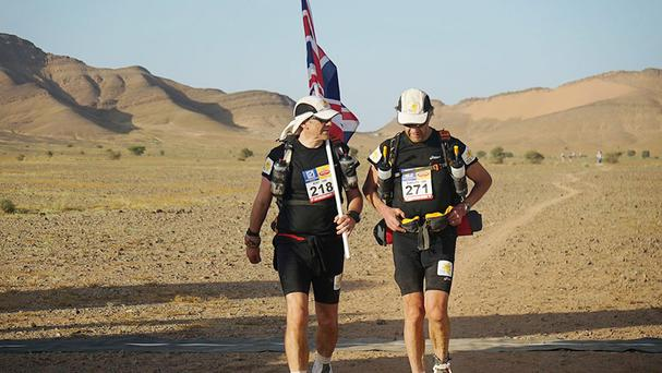 Sir Ranulph Fiennes (right) and his trainer Rory Coleman crossing the finish line of the first stage of his attempt to become the oldest Briton to complete the Marathon des Sables.