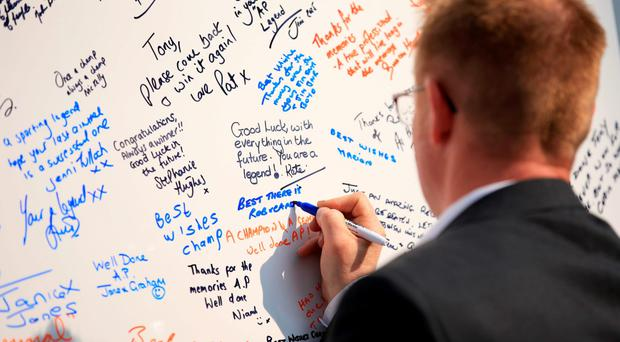 A racegoer writes a message on a board for jockey Tony McCoy for his final ride at the Grand National Festival at Aintree