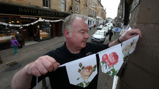 Graham Fleming puts up Bunting in the towns main street, as Local shops in Dunblane High Street decorate their displays in support of local boy Andy Murray ahead of his wedding to Kim Sears.