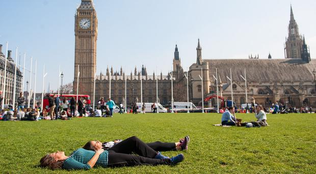Sunbathers enjoy the spring sun in Parliament Square, London.