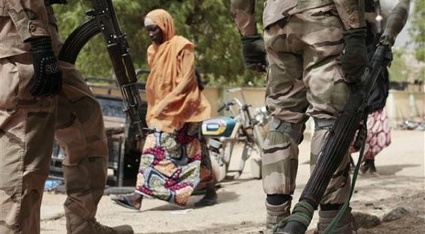 A woman walks past soldiers at a checkpoint in Gwoza, Nigeria, a town newly liberated from Boko Haram (AP)