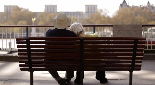 A couple on a bench enjoying the hot weather, on the South Bank in central London