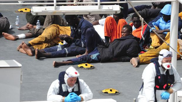 Survivors of the smuggler's boat that overturned off the coast of Libya shelter on the deck of the Italian coastguard ship Bruno Gregoretti in Valletta, Malta (AP)