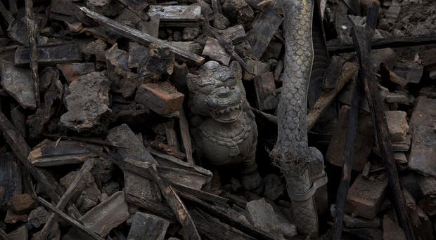 A lion sculpture stands in the rubble caused by Saturday's earthquake in Sakhu, on the outskirts of Kathmandu (AP)