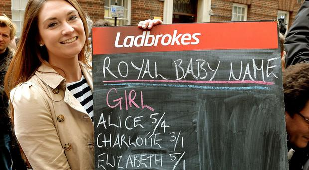 A woman from Ladbrokes holds a blackboard displaying odds on the name after the Duchess of Cambridge gave birth to a girl