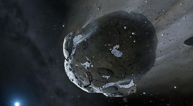 An artist's impression of a water-rich asteroid being torn apart by the strong gravity of a white dwarf star (University of Warwick/PA)