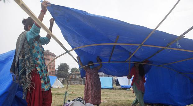 Nepalese women arrange their makeshift tent in Kathmandu following the devastating earthquake which left 2.8m people withouth shelter (AP Photo/Niranjan Shrestha)
