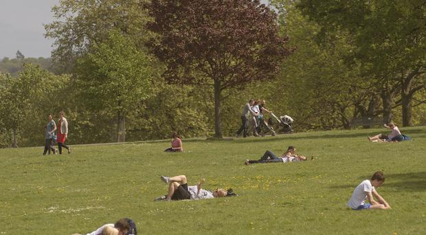 People enjoy the warm weather in Brockwell Park near Herne Hill, London