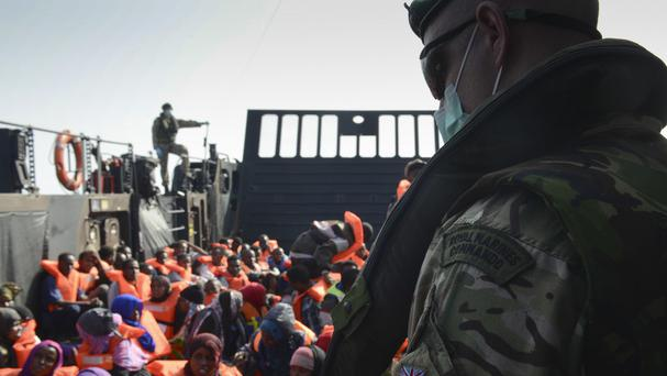 A Royal Marine from HMS Bulwark watches over refugees on a Royal Navy landing craft in the Mediterranean (MoD/PA)