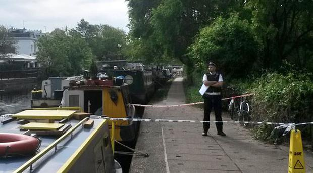 Police at the scene by the Grand Union Canal in west London where the body was found