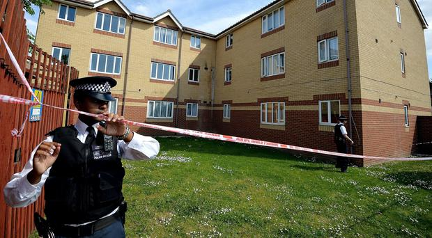 Police outside a flat in Chadwell Heath where the bodies of a mother and her two daughters were found