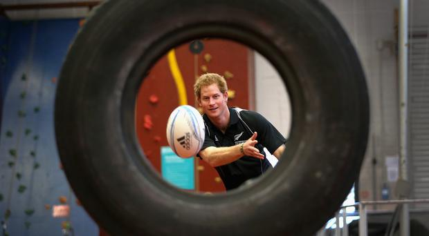 Prince Harry, throws a rugby ball through a tyre as he takes part in a training excercise at the AUT Millennium Institute of Sport and Health, in Auckland.