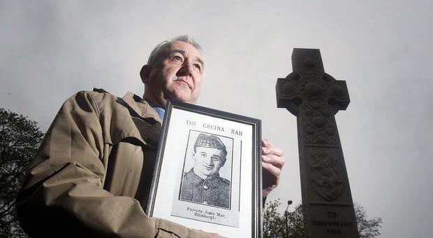 Reverend Iain May, at Rosebank Cemetery in Edinburgh, holds a photograph of his his great uncle, Private John May, who died in the 1915 Quintinshill train disaster that killed 214 soldiers and 12 civilians.