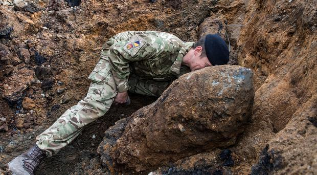 An Army expert checks the fuse on a Second World War bomb found in Bermondsey, south-east London, in March