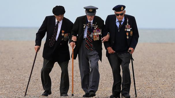 Dunkirk veterans James Baynes, Arthur Taylor and Michael Bentall walk along a beach