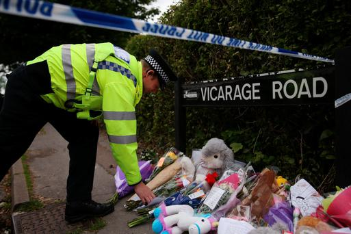 A police officer lays a bunch of flowers near the home of three people who were found dead