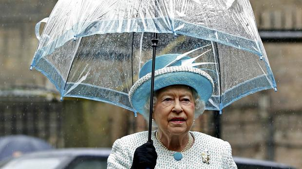 The Queen holds an umbrella as she stands in the rain during her visit to Lancaster Castle, after she arrived at the historic city by royal train