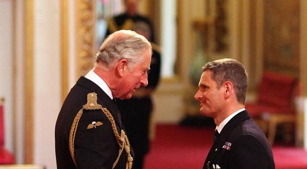 Lieutenant Commander Christopher Gotke is decorated with the Air Force Cross by the Prince of Wales during an investiture ceremony at Buckingham Palace
