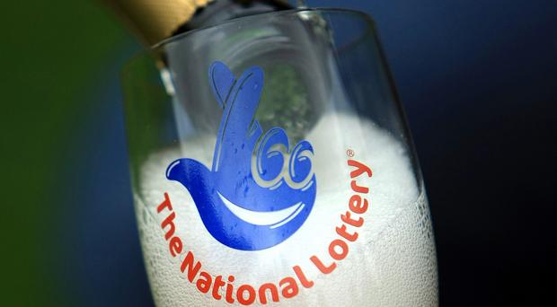 Champagne is poured into a National Lottery branded champagne glass flute.