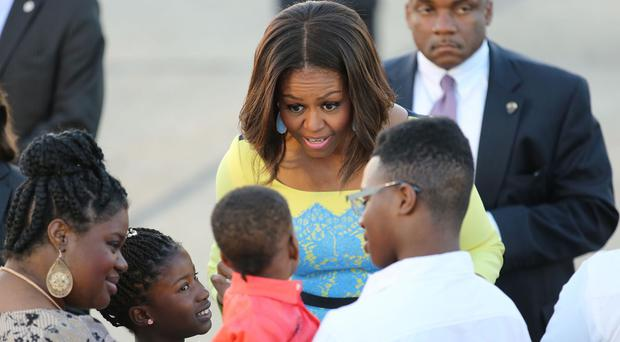 Michelle Obama greets a child as she arrives at Stansted Airport