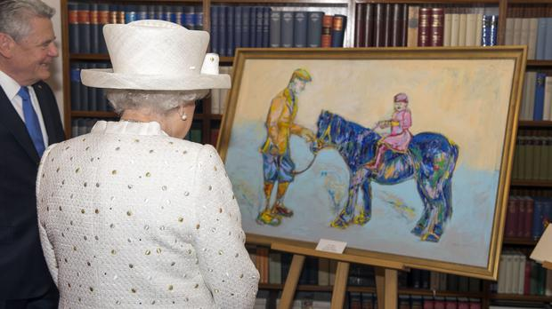 The Queen is presented with a painting by Germany's Federal President Joachim Gauck at his official Berlin residence, Bellevue Palace