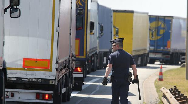 A French police officer checking lorries on the main road into Calais ferry port as migrants have been trying to board UK-bound lorries