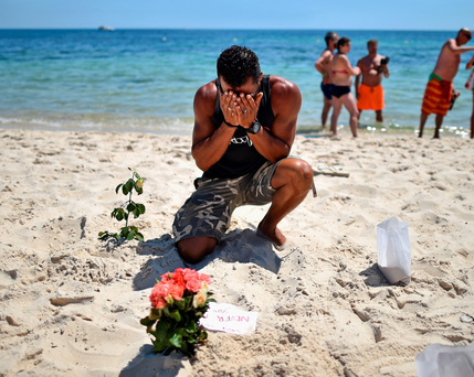 A man breaks down at the Tunisia murder scene