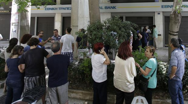 People queuing to use ATMs at a bank in central Athens (AP)